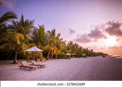 Amazing tropical sunset with romantic mood, two sun chairs and umbrella, beach landscape, soft colored sky and calm beach scene background. Exotic travel destination concept