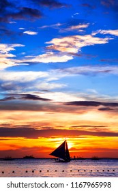 amazing tropical sunset and silhouette of sailing boats in Boracay island, Philippines