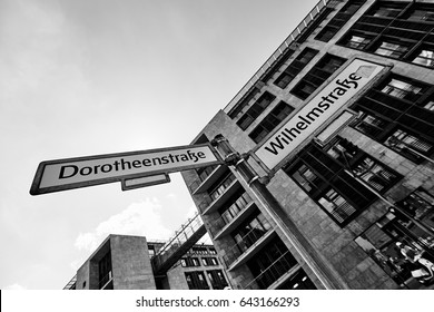 Amazing urban lifestyle view with facade of modern building, sunny sky and pillar pointer with plates in European city in black and white