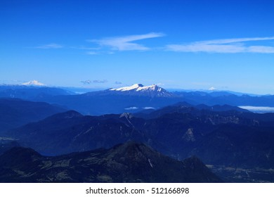 amazing view from the active vulcan villarica in chile with deep valleys and another vulcan with a white peak