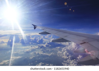 Amazing view from airplane window, Beautiful of Airplane wing with clouds and blue sky on sunset light background