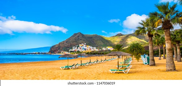 Amazing view of beach las Teresitas with yellow sand, umbrellas, longues and palm trees. Location: Santa Cruz de Tenerife, Tenerife, Canary Islands. Artistic picture. Beauty world.