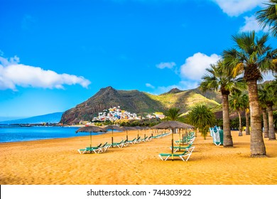 Amazing view of beach las Teresitas with yellow sand, umbrellas, longues and palm trees. Location: Santa Cruz de Tenerife, Tenerife, Canary Islands. Artistic picture. Beauty world