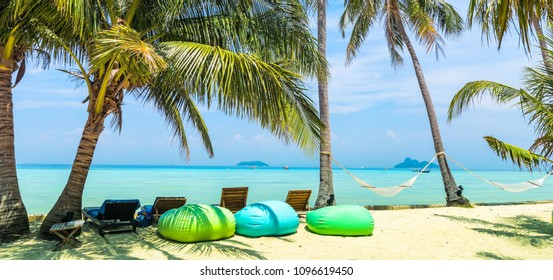 Amazing view of beautiful beach with palm trees, armchair-pears, chaises and transparent turquoise water. A great place to relax. Location: Ko Phi Phi Don island, Krabi province, Thailand, Andaman Sea
