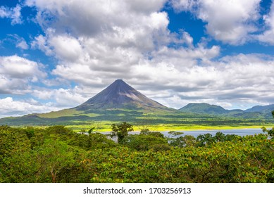 Amazing view of beautiful nature of Costa Rica with smoking volcano Arenal background. Panorama of volcano Arenal reflected on wonderful picturesque lake, La Fortuna, Costa Rica. Central America.
