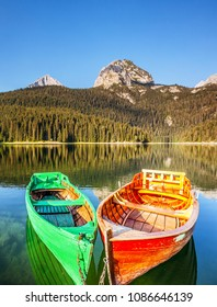 Amazing view of Black lake and wooden boats. Location National park Durmitor, Montenegro, Balkans, Europe. Scenic image of exotic nature landscape. Splendid summer scene. Discover the beauty of earth.
