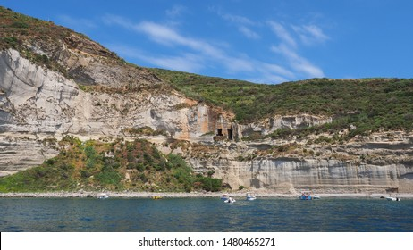 Amazing view to colorful steep rock with carved holes or caves in the hillside. Small boats in the water. Beautiful landscape. Ponza. Pontine Islands. Italy. Boat trip. View of the Tyrrhenian Sea.