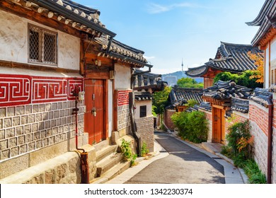 Amazing view of cozy old narrow street and traditional Korean houses of Bukchon Hanok Village in Seoul, South Korea. Seoul Tower on Namsan Mountain is visible on blue sky background. Scenic cityscape.