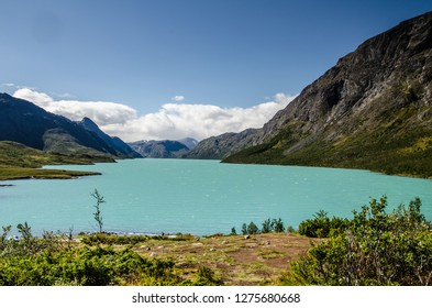 Amazing view of the crystal blue lake Gjende in Jotunheimen National Park with beautiful mountains behind and blue sky