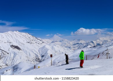 Amazing view of damavand peak with two skiers and their snowboards and ski gears on mountain in snow at Dizin Ski Resort. Iran