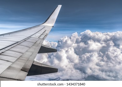 Amazing view of the Dramatic Cumulus clouds from the window side seat of an Airplane. Airplane wings along with its all components are visible. Sky above is clear and clouds are fluffy as cotton balls