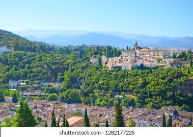 Amazing view of famous Alhambra palace complex surrounded by forests and city Granada taken on a sunny day. A beautiful sample of Islamic architecture. One of the most popular Spanish tourist sites.