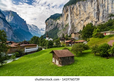 Amazing view of famous Lauterbrunnen town in Swiss Alps valley with beautiful Staubbach waterfalls in the background, Switzerland.