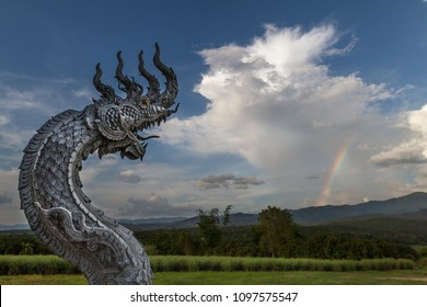 Amazing view with a great traditional thai naga dragon sculpture breathing huge white clouds as fire and smoke