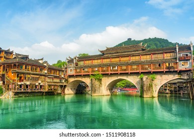 Amazing view of the Hong Bridge (Rainbow Bridge) over the Tuojiang River (Tuo Jiang River) and old traditional Chinese wooden riverside houses in Phoenix Ancient Town (Fenghuang County), China.