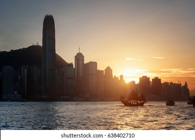 Amazing view of the Hong Kong Island skyline at sunset. Skyscrapers in downtown of Hong Kong are visible from Kowloon side. Tourist boats and traditional Chinese sailing ship in Victoria harbor.