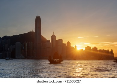Amazing view of the Hong Kong Island skyline at sunset. Skyscrapers in downtown of Hong Kong are visible from Kowloon side. Tourists on traditional Chinese sailing ship crosses Victoria harbor.