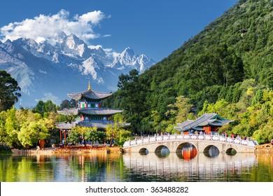 中国雲南省麗江にあるジェイド・ドラゴン・スノウ・マウンテンとブラック・ドラゴン・プールの素晴らしい眺め。池と月を抱きしめる「水汲み橋」がジェイド・スプリング・パークにある。