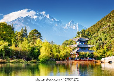 Amazing view of the Jade Dragon Snow Mountain and the Moon Embracing Pavilion on the Black Dragon Pool in the Jade Spring Park, Lijiang, Yunnan province, China.