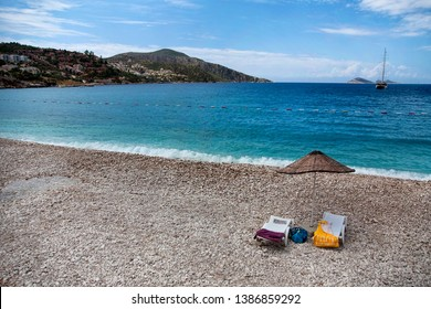 Amazing view of Kalkan beach with umbrella and two sun loungers