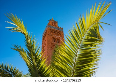 Amazing view of Koutoubia Mosque minaret located at medina quarter of Marrakesh, Morocco, against a deep blue sky and palm leaves