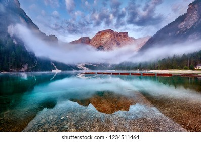Amazing view of Lago di Braies (Braies lake, Pragser wildsee) at sunrise. Trentino Alto Adidge, Dolomites mountains, South Tyrol, Italy, Europe. Boats at the lake. Fanes-Sennes-Braies national park.