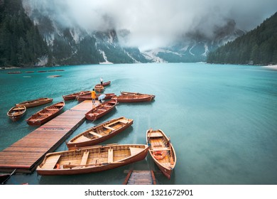 Amazing view of Lago di Braies (Braies lake, Pragser wildsee) in clouds and rain. Trentino Alto Adidge, Dolomites mountains, South Tyrol, Italy. Boats at the lake. Fanes-Sennes-Braies national park.