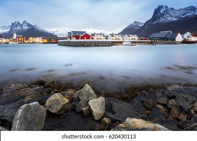 Amazing view of Lofoten islands,village Reine with red houses near clear green water and beautiful mountains in evening