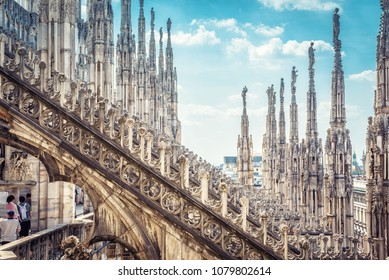 Amazing view of Milan Cathedral roof (Duomo di Milano) in summer, Milan, Italy. Beautiful luxury terrace on the top of Milan Cathedral with rows of Gothic pinnacles on the blue sky background.