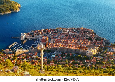 Amazing view from mountain at Old town of Dubrovnik in Croatia. Sunset in Adriatic sea, harbor with yachts, cable road, all is here.