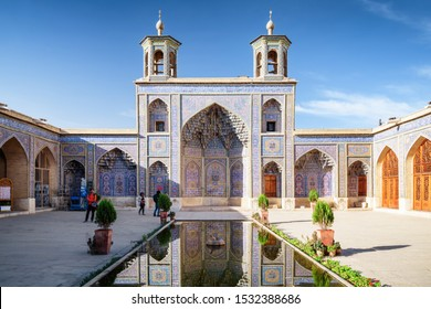 Amazing view of the Nasir al-Mulk Mosque (Pink Mosque) reflected in pool in the middle of traditional courtyard in Shiraz, Iran. Gorgeous Persian exterior of the Muslim place. Islamic architecture.