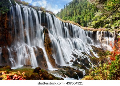 Amazing view of the Nuo Ri Lang Waterfall (Nuorilang) among woods and mountains in Jiuzhaigou nature reserve (Jiuzhai Valley National Park) of Sichuan province, China. Fantastic sunny landscape.