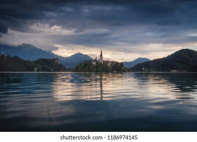 Amazing View On Bled Lake on Sunset. Europe. View on Island with Catholic Church in Bled Lake with Castle and yellow sky on the Background.
