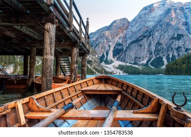 Amazing view on lake Lago di Braies (Braies lake, Pragser wildsee) at sunset light in Dolomiti mountains, South Tyrol, Trentino, Italy. Stunning view on lake from wooden rowing boat, Alps mountains.