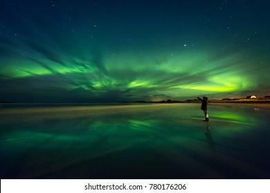 Amazing view on the northern lights, beautiful green lights on the sky at night, traveler woman enjoying Aurora, merry dancers, beautiful phenomenon in Norway