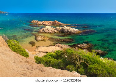 Amazing view on Platja de Santa Cristina in Lloret de Mar, Costa Brava, Spain. Rocks in turquoise water on summer sandy beach in mediterranean. Paradise lagoon in spanish resort.
