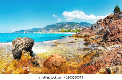 Amazing view on rocky tropical beach on sunny summer day in Alanya, Turkey. Turkish seascape with mountains and rocks on coastline. Blue clear sky, sea and tropic nature. Lagoon of mediterranean sea