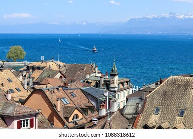 Amazing view over the roofs of old Nyon town at blue Geneva lake or Lac Leman with sailboats and ship and mountains with snow tops at background, Switzerland, Europe