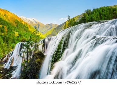 Amazing view of the Pearl Shoals Waterfall among scenic wooded mountains and evergreen forest in Jiuzhaigou nature reserve (Jiuzhai Valley National Park), China. Beautiful autumn landscape at sunset.