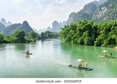 Amazing view of small tourist bamboo rafts sailing along the Yulong River among green woods and karst mountains at Yangshuo County of Guilin, China. Yangshuo is a popular tourist destination of Asia.