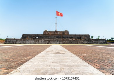 Amazing view of a square and the flag of Vietnam (red flag with a gold star) fluttering over a tower of the Citadel on blue sky background in Hue, Vietnam. Within the Citadel is the Imperial City.