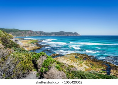 Amazing view to stunning rocky sandy beach deep blue water of southern ocean antarctica on warm sunny day with blue sky after hiking on to South Cape Bay, South-West National Park, Tasmania, Australia