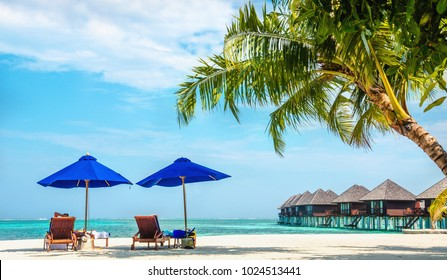 Amazing view of sun loungers under blue umbrellas on the background of Maldives huts, Maldives