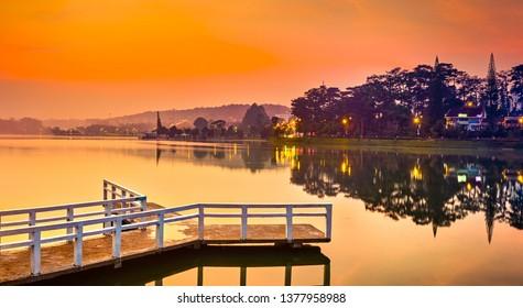 Amazing view of sunrise over Xuan Huong Lake, Dalat, Vietnam. Pier on the foreground. Landscape photo. Panorama