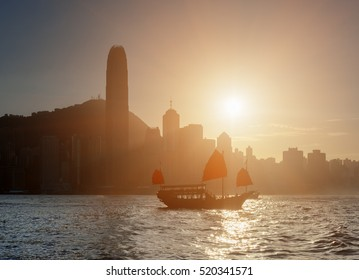 Amazing view of traditional Chinese wooden sailing ship with red sails in Victoria harbor at sunset. Tourist sailboat and Hong Kong Island skyline. Silhouettes of skyscrapers are visible in background
