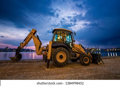 Amazing view at yellow excavator with a shovel at a construction site in a beautiful twilight