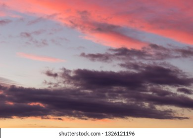 Amazing vivid purple and pink colors of a sunlit, contrasty clouds on a sunset sky