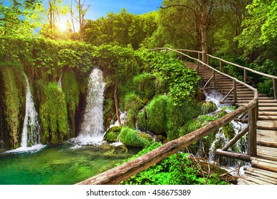 Amazing waterfall in Plitvice Lakes National Park, Croatia, Europe. Majestic view with turquoise water, wooden handrail stairs, and sunset sunny beams, travel destinations background