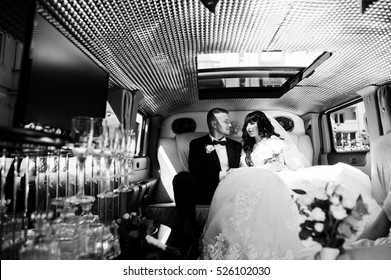 Amazing wedding couple inside elegance limousine at their awesome wedding day. Black and white photo