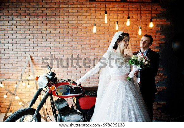 Amazing wedding couple posing with a huge old motorcycle in a room full of lights.